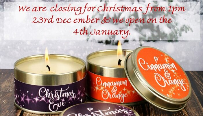 Two burning Christmas Candles against a snowy backdrop and giving Christmas closing times of 23 December to 4 January