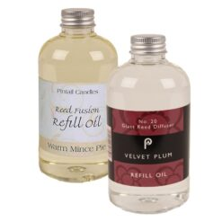 Two bottles of reed diffuser oil. Warm Mince Pie in a beige label and Velvet Plum in a deep red label.